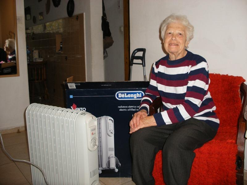 Oude vrouw bij kachel